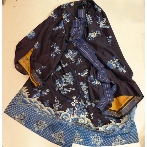 11 - A Chinese silk robe, decorated with stylised flowers and waves on a dark blue ground, with light blu...