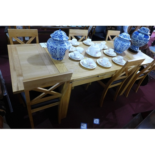 407 - A contemporary solid oak extending dinning table, with six matching oak chairs, H.77 W.230 D.90cm (t...
