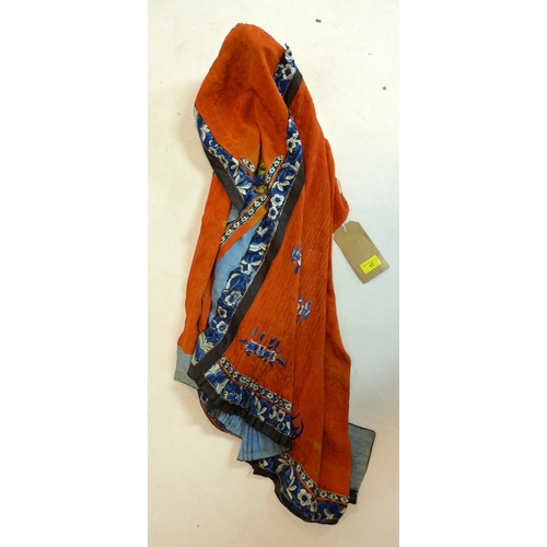 17 - A Chinese silk skirt, decorated with stylised flowers in blues and greens on an orange background...
