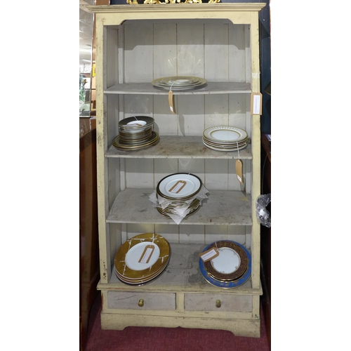 212 - A 20th century distressed painted open bookcase, three shelves above two small drawers, H.180 W.94 D...