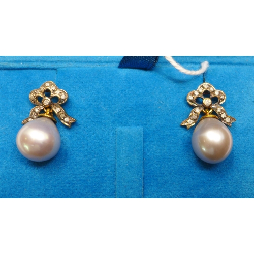 16 - A boxed pair of 18ct yellow gold earrings, with diamond-studded bow tops each suspended by a pear-sh...