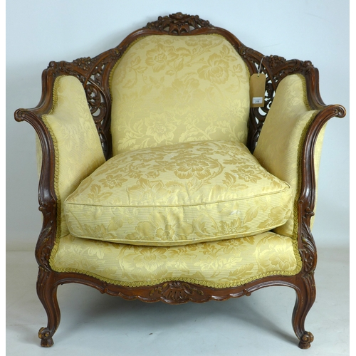 216 - An early 20th century Rococo style carved walnut armchair...