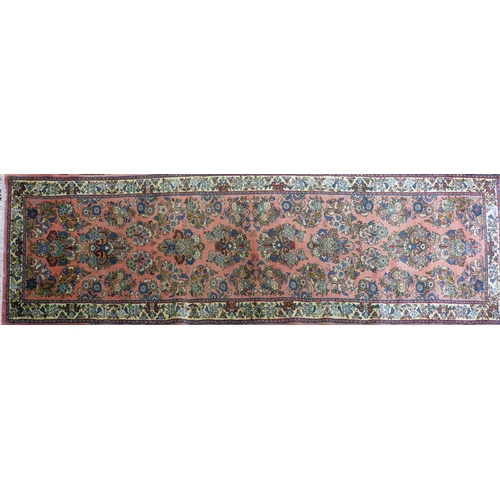 81 - A North West Persian Sarouk runner, repeating stylised floral motifs on a pink ground, within stylis...