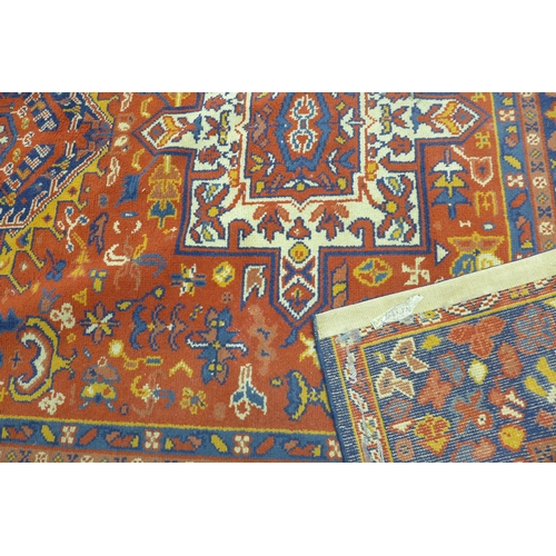 93 - A Heriz carpet with three geometric medallions, on a red and blue ground, contained by geometric bor...
