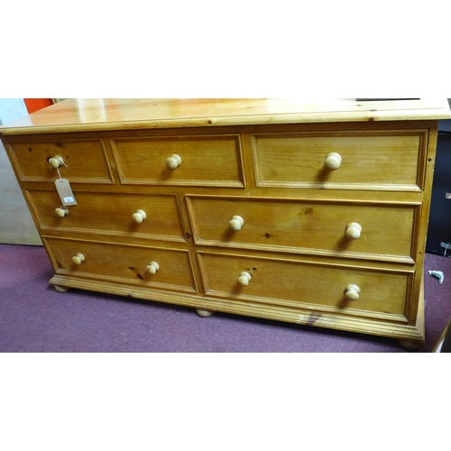 359 - A 20th century long pine chest of 3 short over 4 long drawers, on bun feet, H.84 W.164 D.55cm...