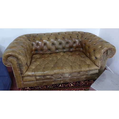 143 - A 20th century brown leather chesterfield sofa...