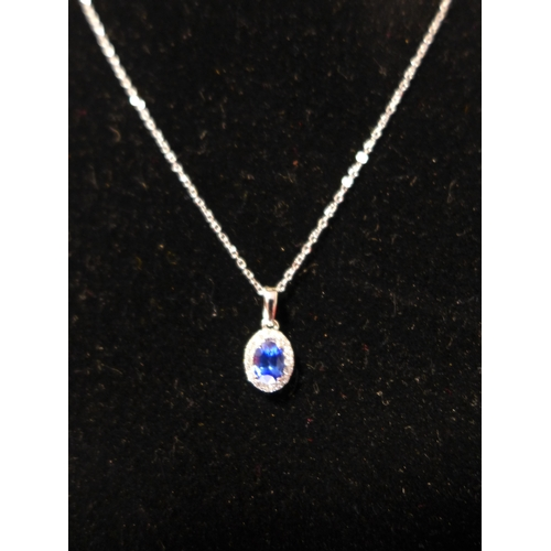 83 - A boxed 18ct white gold brilliant-cut diamond and sapphire pendant centrally set with an oval facete...