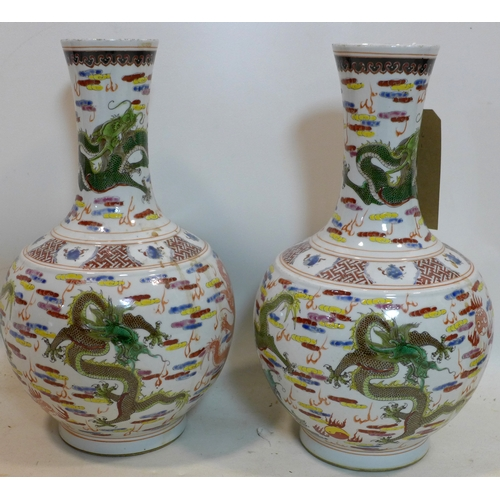 25 - A pair of Chinese, Republic period famille rose bottle vases decorated with dragons chasing the pear...