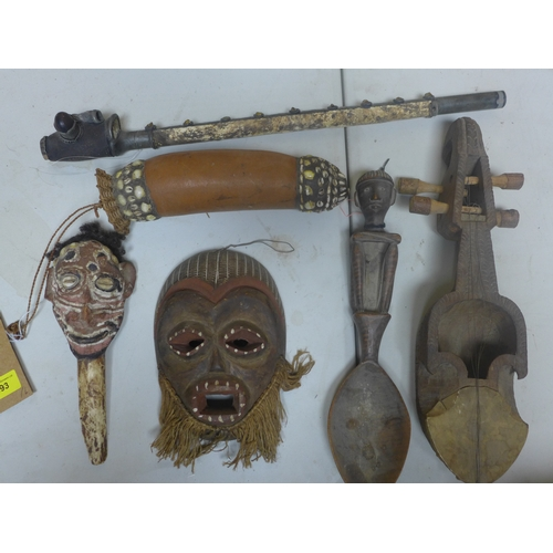 293 - A small collecton of tribal art to include a mask, blow pipe, spoon, instrument, mask on bone stick ...