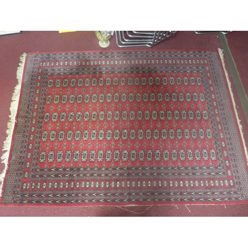 380 - A 20th century Bokhara carpet with repeating gull motifs, on a red ground, contained by geometric bo...