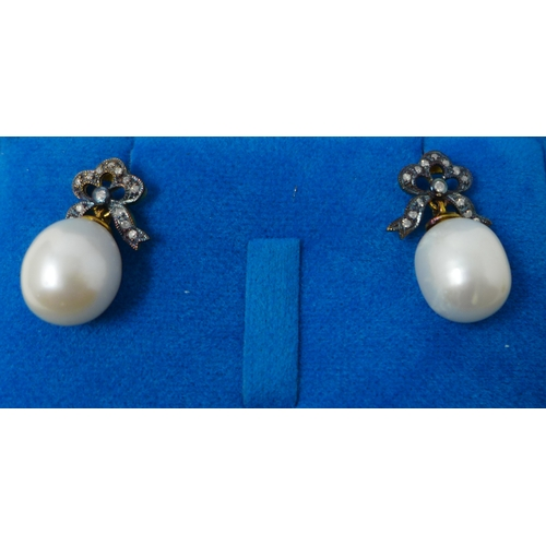 7 - A boxed pair of yellow gold diamond studded earrings each set with a bow suspended by a large cream-...