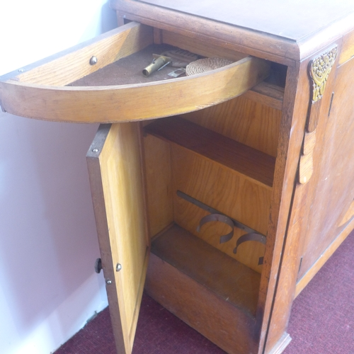 298 - An Art Deco oak drinks cabinet, with two cupboard doors revealing shelves and two small drawers, one...