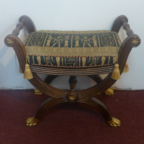 307 - A Regency style mahogany stool, with Egyptian style design upholstered seat, parcel gilded with scro...
