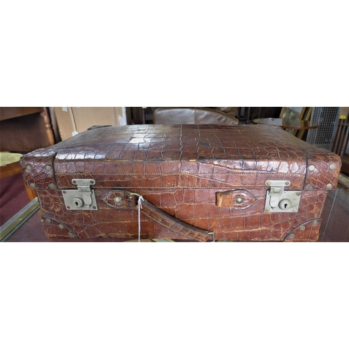 4 - A large, early 20th century, crocodile skin suitcase with fitted green leather interior, H: 21 x W: ...