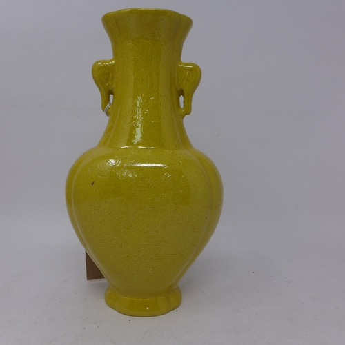175 - A Chinese porcelain vase in the famille jaune glaze with twin elephant handles and incised dragon de...