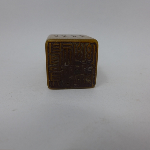 200 - A Chinese, orange soapstone seal with a carved, smiling Buddha to top and character marks to front p...