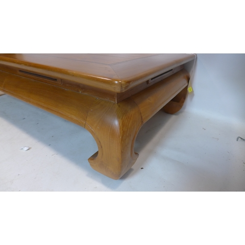 24 - An Asian hardwood coffee table on thick carved legs, H: 33 x W: 120 x D: 68cm...
