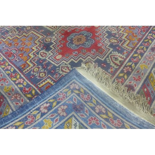 98 - An antique Khotan East Turkoman carpet, with geometric medallions on a blue ground, within geometric...