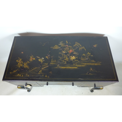 256 - A black lacquered Chinoiserie desk, decorated with houses, figures, flowers and birds, having three ...