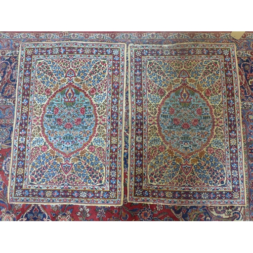 20 - A pair of early 20th century central Persian Kirman rugs, with floral medallion surrounded by floral...