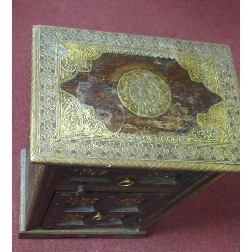15 - An Indian brass mounted padauk wood bedside table, with one small drawer and one cupboard door, havi...