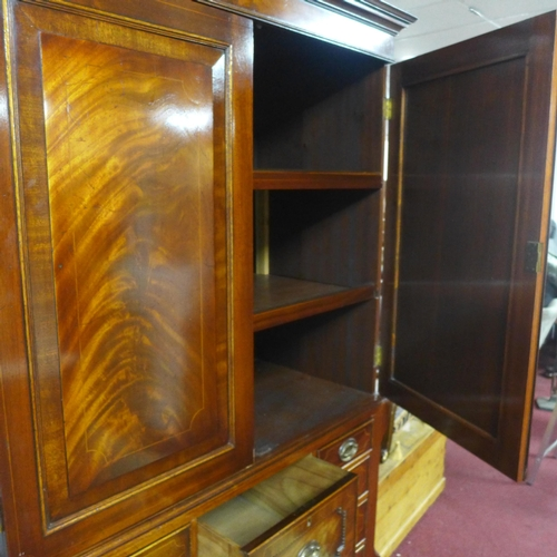 17 - An early 20th century Regency style inlaid mahogany linen press, with two cupboard doors above an ar...
