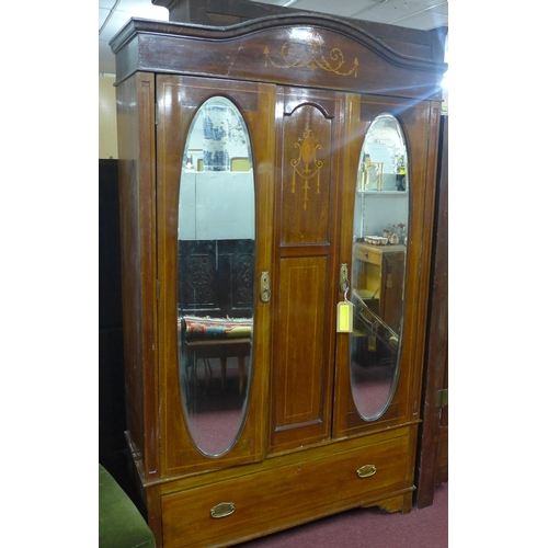 18 - An early 20th century mahogany wardrobe, the arched pediment above two cupboard doors having bevelle...