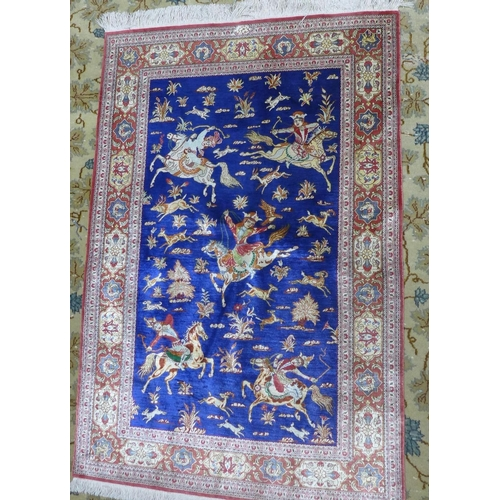 21 - An antique Persian Qum silk rug, signed, with hunting design on a blue ground, within floral border,...