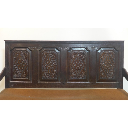 23 - An oak bench with panelled high back with floral decoration, on cabriole feet, H.106 W.149 D.66cm...