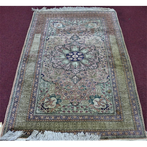 27 - A Persian part silk rug, central floral medallion on a pink and cream ground with stylised bird and ...
