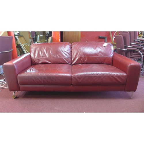 32 - A contemporary red leather sofa raised on chrome feet...