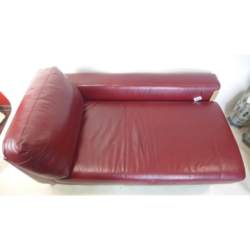 33 - A contemporary red leather chaise longue  raised on chrome feet...