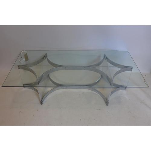 40 - A Merrow Associates glass top coffee table, raised on chrome and perspex base, glass had slight repa...