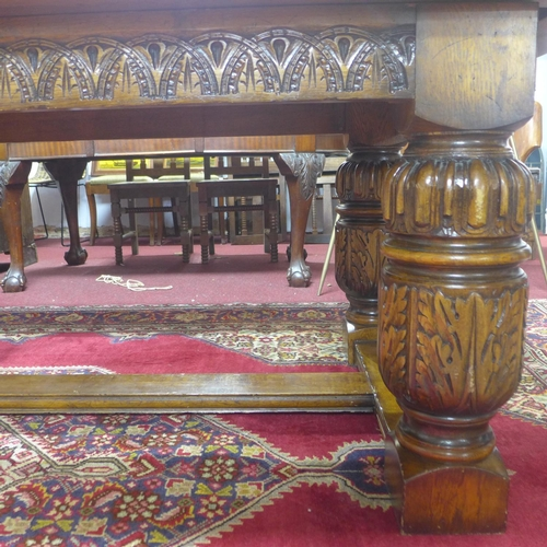 44 - A large 19th century oak refectory dining table, the carved supports joined by stretchers, H.76 W.22...