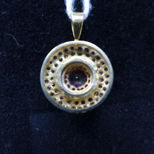 49 - An antique, 18ct yellow gold circular pendant set to the centre with a round, faceted amethyst to a ...