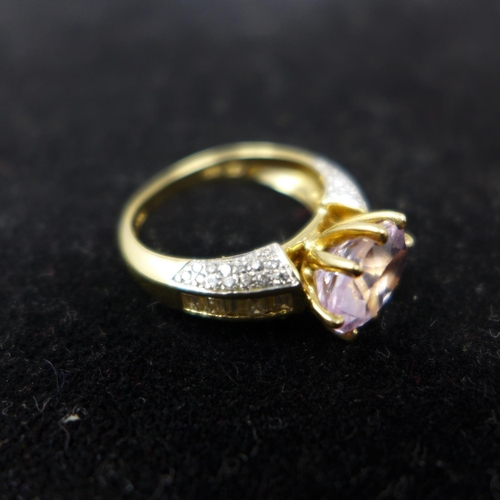 51 - An 18ct yellow gold ring set to the centre with a large, faceted natural oval, pink morganite in an ...