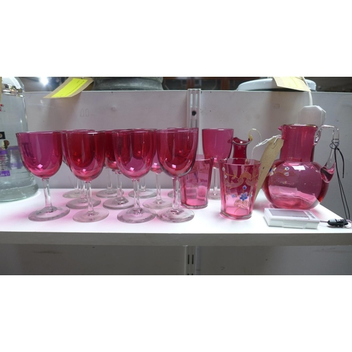 60 - A collection of cranberry glass to include a painted Victorian jug and matching pair of glases...