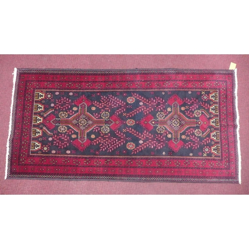 76 - A North East Persian Meshad Belouch rug, double pole medallion with repeating petal motifs within st...