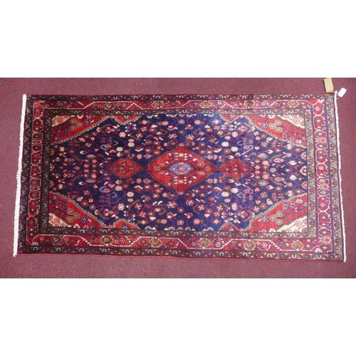 79 - A North West Persian Nahawand rug, triple pole medallion with repeating petal motifs on a sapphire f...
