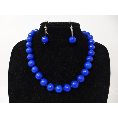 84 - A boxed lapis lazuli suite comprising of polished bead necklace L: 44cm, bracelet L: 19cm and earrin...