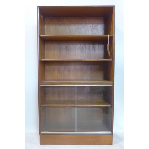 112 - A 20th century 'Minty, Oxford' teak bookcase, with adjustable shelves above 2 sliding glass doors, H...