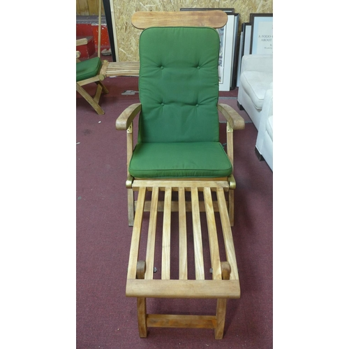 113 - A pair of sun loungers with green cushions...