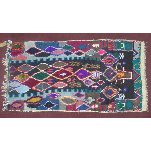 136 - A vintage Moroccan Berber Azilal rug, with multi-coloured diamond motifs on a black ground, 220 x 11...