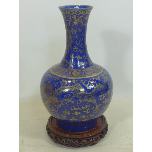 140 - A late 19th / early 20th century Chinese powder blue and gilt vase, decorated with dragons chasing t...