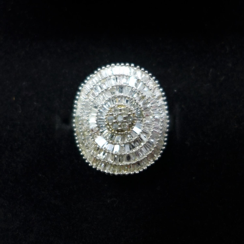 197 - A boxed Art Deco style diamond ring in platinum-plated silver of convex disk form studded with bague...