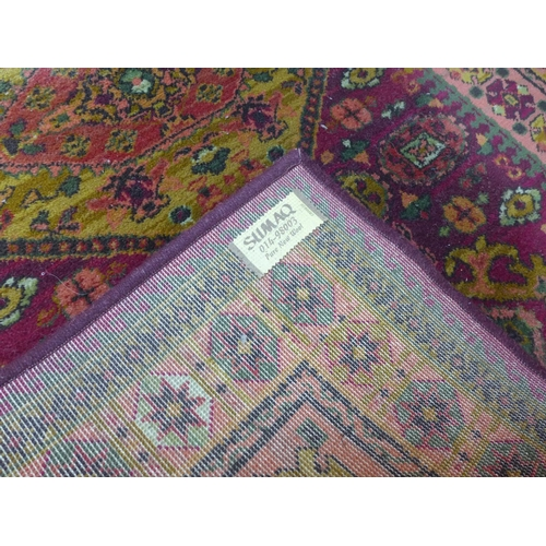 208 - A Persian style woollen rug, three medallions on a purple and rouge ground, within floral geometric ...