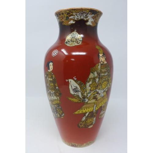 216 - A 19th century Japanese satsuma vase, decorated with figures and flowers, on a red ground, bearing s...