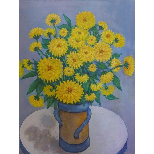 228 - An oil on canvas of yellow chrysanthemums in a vase on a blue ground, unsigned, 55 x 45cm...