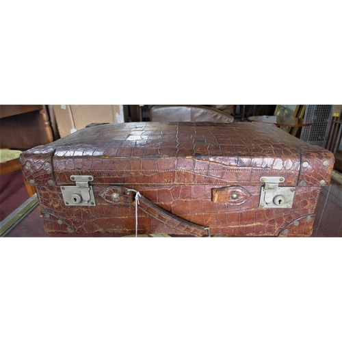317 - WITHDRAWN- A large early 20th century, crocodile skin suitcase with fitted green leather interior, H...