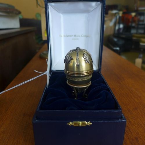 344 - A boxed sterling silver egg and stand by St James House Collection set to the top with a circular mo...